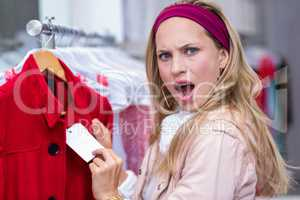 Shocked woman showing price tag to camera