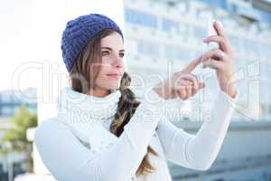 Cold brunette in warm clothes taking photos