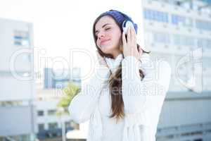 Cold brunette in warm clothes listening music