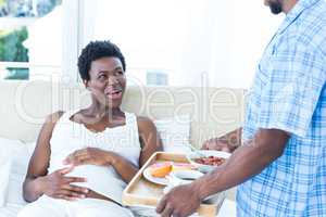Husband bringing breakfast for pregnant wife