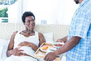 Husband bringing breakfast for pregnant wife