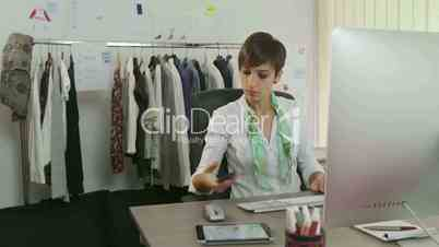 Confident businesswoman, young woman working as fashion designer, manager with computer in studio, talking on mobile phone. People, career, success, business, industry, busy worker in office