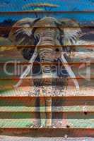 Elephant mural on wooden shack in sunshine