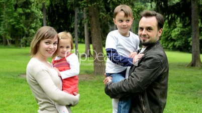 family (middle couple in love, cute girl and small boy) turn to camera and smile to camera in the park