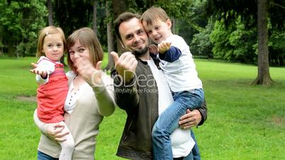 family (middle couple in love, cute girl and small boy) welcome in the park