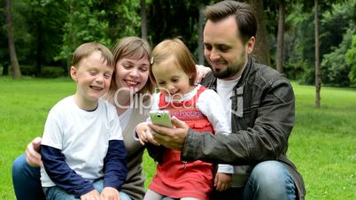 family (middle couple in love, cute girl and small boy) together work on smartphone - park