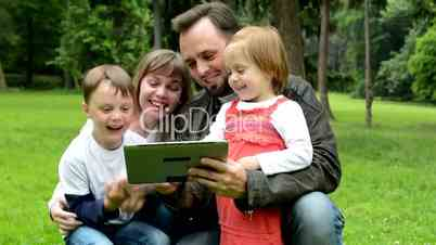 family (middle couple in love, cute girl and small boy) together work on tablet - park
