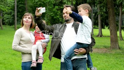family (middle couple in love, cute girl and small boy) take a photo with smartphone - monuments (travel) - park
