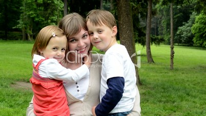 family (mum, little boy and cute girl) smile to camera - park