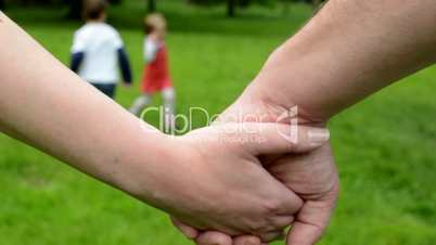 family - man and woman holding hands - detail: focus on hands - children (siblings - little boy and cute girl) playing in the park in the background