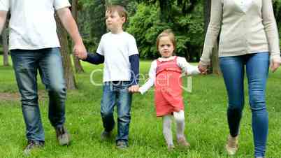 family (middle couple in love, cute girl and small boy) walking in park from distance to camera