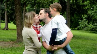 Family (middle couple in love, cute girl and small boy) give a kiss together in park