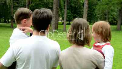 family (middle aged couple in love, boy and girl) relax in park and point to distance - shot from back