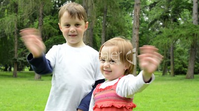 childrens (young boy and little girl (siblings)) wave with hands and smile to camera  - park