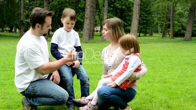 parents (mother and father) teach children (boy and girl) to count on the fingers - park