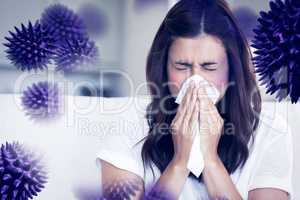 Composite image of brunette sneezing in a tissue