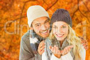 Composite image of attractive couple in winter fashion smiling a