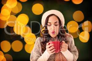 Composite image of brunette in winter clothes holding hot drink