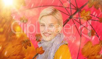 Composite image of smiling woman holding an umbrella