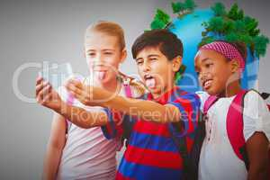 Composite image of school kids taking selfie in school corridor