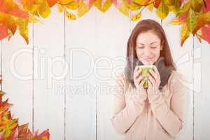 Composite image of smiling brunette smelling hot beverage