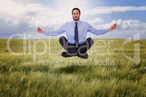 Composite image of businessman in suit sitting in lotus pose
