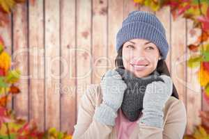 Composite image of smiling brunette wearing warm clothes