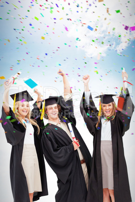 Composite image of three students in graduate robe raising their