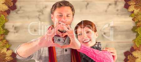 Composite image of couple making a heart shape