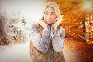 Composite image of blonde in winter clothes smiling