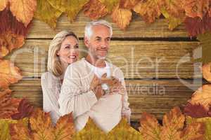 Composite image of cheerful wife embracing husband