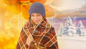 Composite image of smiling brunette with checked blanket