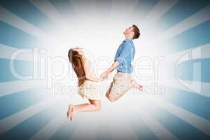 Composite image of cheerful young couple jumping