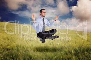 Composite image of relaxed businessman sitting in lotus pose