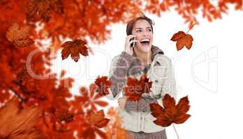 Composite image of laughing cute brunette in winter fashion phon