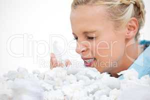 Composite image of ill woman sneezing into tissue