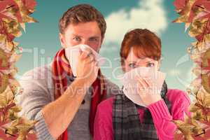 Composite image of couple blowing noses into tissues