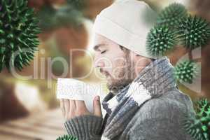 Composite image of handsome man in winter fashion blowing his no