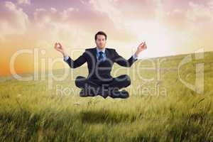 Composite image of calm businessman sitting in lotus pose