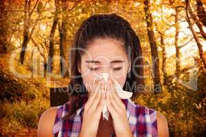 Composite image of close-up of sick woman sneezing in a tissue