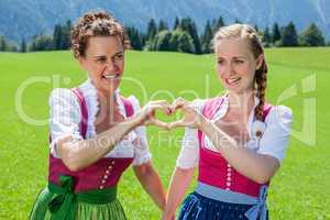 Zwei Frauen im Dirndl bilden ein Herz mit Ihren Händen