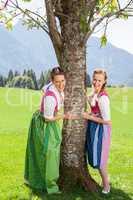 Zwei lächelnde Frauen Im Dirndl halten sich an einem Baum fest.