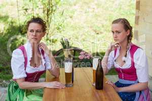 Mutter und Tochter sitzen im Dirndl an einem Tisch vor einem Glas Bier.