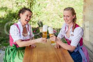 Zwei Frauen prosten sich mit einem Glas Bier zu