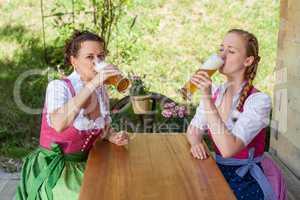 Zwei Frauen im bayerischen Dirndl beim Bier trinken