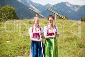 Zwei Bäuerinnen im Dirndl mit Rechen auf einer Almwiese