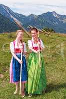 Zwei Frauen im Dirndl mit Rechen haben Spaß bei der Arbeit