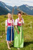 Zwei freudige Frauen im Dirndl mit Rechen haben Spaß bei der Arbeit