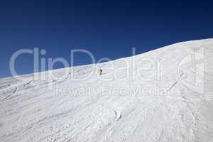 Skier on slope in sun day