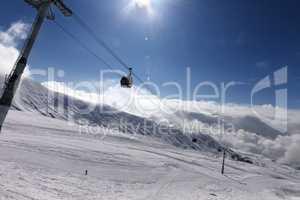 Gondola lift and ski slope at nice sunny day